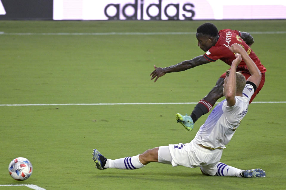 Orlando City defender Robin Jansson, front, defends against a shot attempt by Toronto FC midfielder Richie Laryea (22) during the first half of an MLS soccer match Saturday, June 19, 2021, in Orlando, Fla. (AP Photo/Phelan M. Ebenhack)