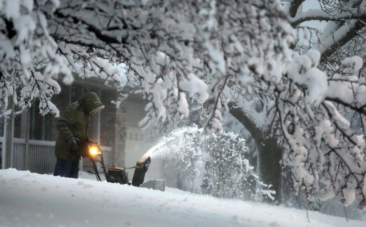 A local resident clears snow from his driveway after an overnight snowfall left many schools and businesses closed for the day, Thursday, Dec. 20, 2012, in Urbandale, Iowa. (AP Photo/Charlie Neibergall)