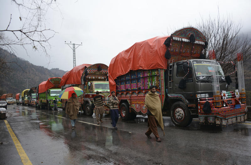 """Pakistani Kashmiris walk past India-bound cargo trucks, parked as road is closed to Indian Kashmir, in the border town of Chakoti at Line of Control in Pakistani Kashmir, Tuesday, Feb. 26, 2019. Pakistan said India launched an airstrike on its territory early Tuesday that caused no casualties, while India said it targeted a terrorist training camp in a pre-emptive strike that killed a """"very large number"""" of militants. (AP Photo/Abdul Razaq)"""