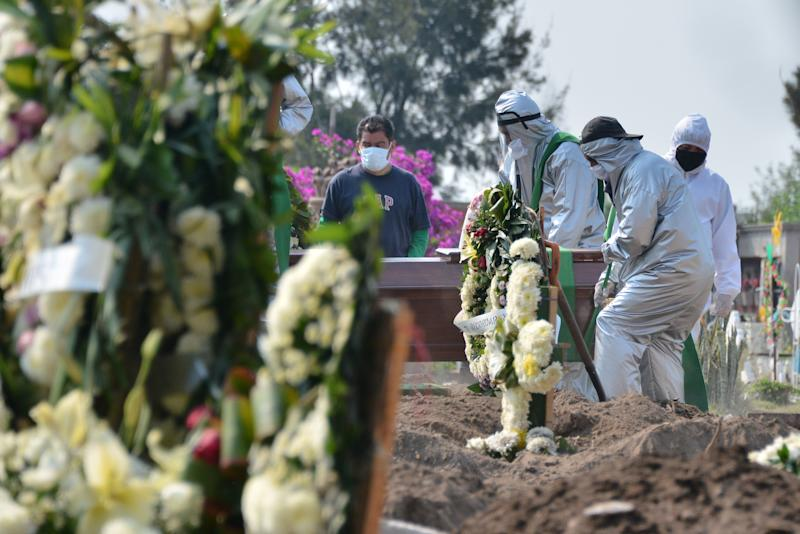 Funeral workers wear protective suit equipment while carrying a coffin of a person who died of Covid-19 to bury he in a grave located at special section intended for COVID-19 victims in a Mexican cemetery. Source: Barcroft Media via Getty Images