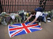 <p>A member of the public lays a Union Jack Flag next to floral tributes outside Buckingham Palace on April 9. </p>