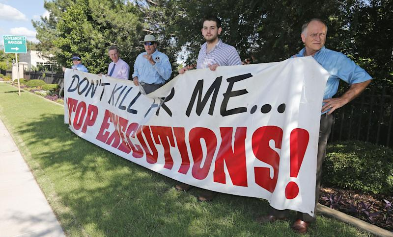 Protestors hold a sign against the death penalty outside the governor's mansion in Oklahoma City, Tuesday, June 18, 2013, protesting the execution of James DeRosa in McAlester, Okla. DeRosa was killed by lethal injection at the Oklahoma State Penitentiary in McAlester. He was the second inmate the state executed this year. (AP Photo/Sue Ogrocki)