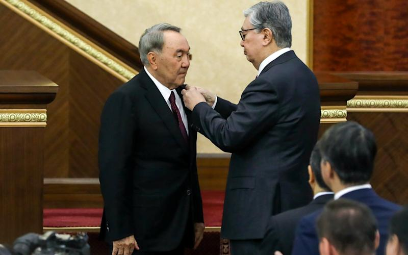 Kazakhstan's new president Kassym-Jomart Tokayev pins a medal on Nursultan Nazarbayev, who will remain head of the security council and ruling party, on Tuesday - TASS / Barcroft Media