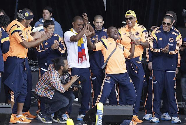 Colombia's soccer player Pablo Armero, third right, dances as teammates watch during the team's homecoming celebration in honor of their World Cup showing, in Bogota, Colombia, Sunday, July 6, 2014. Thousands of fans turned out for the Sunday homecoming of superstar James Rodriguez, third from right, his teammates and coach Jose Pekerman following their 2-1 loss to Brazil in the quarterfinals on Friday. (AP Photo/Fernando Vergara)