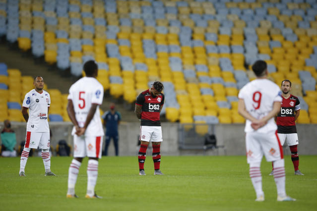 Players of Bangu, wearing white uniforms, and Flamengo pay a minute of silence for the victims of the coronavirus prior to a Rio de Janeiro soccer league match at the Maracana stadium in Rio de Janeiro, Brazi, Thursday, June 18, 2020. Rio de Janeiro's soccer league resumed after a three-month hiatus because of the coronavirus pandemic. The match is being played without spectators to curb the spread of COVID-19. (AP Photo/Leo Correa)