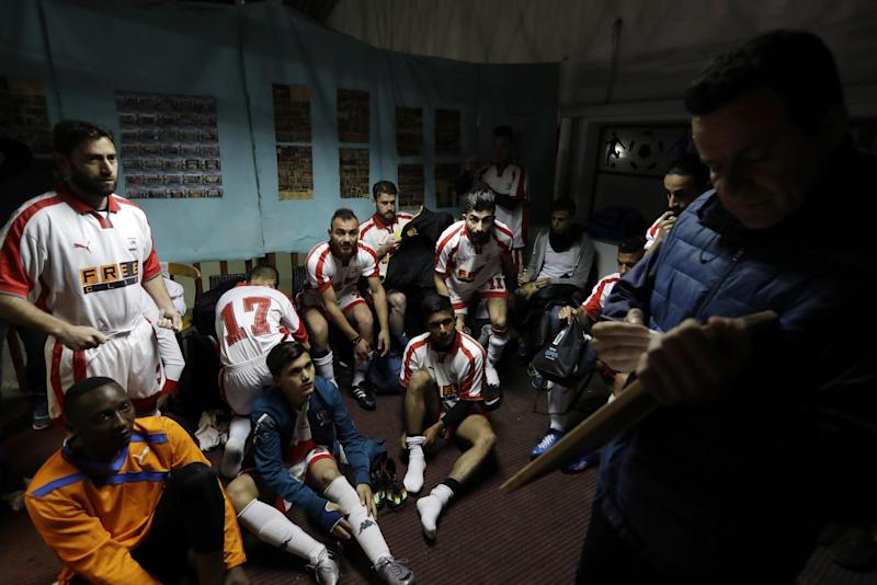 In this Sunday, Feb. 5, 2017, coach of Hope Refugee Football Club Antreas Sampanis, right, gives directions to his players before a soccer match in western Athens. On weekends they play in an amateur league against teams made up of professional groups like lawyers, telecom workers, and accountants. (AP Photo/Thanassis Stavrakis)