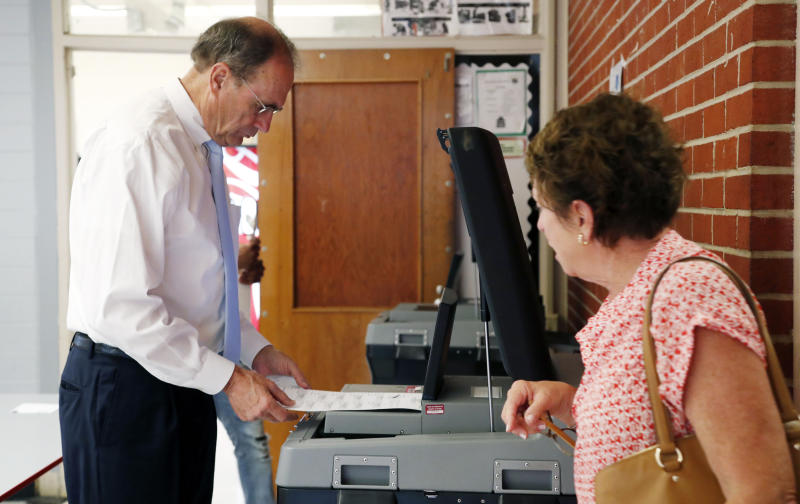 "Mississippi Secretary of State Delbert Hosemann, a Republican candidate for lieutenant governor, left, studies his candidate choices as his wife, Lynn Hosemann, urges him to ""vote"" by sliding the ballot into a reader, during the party primary at a Jackson, Miss., precinct, Tuesday, Aug. 6, 2019. (AP Photo/Rogelio V. Solis)"
