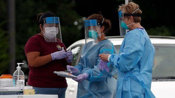 PHOTO: Medical personnel handle test samples at a community coronavirus testing site operated by Cone Health and the county Health Department in Burlington, N.C., July 9, 2020. (Gerry Broome/AP)