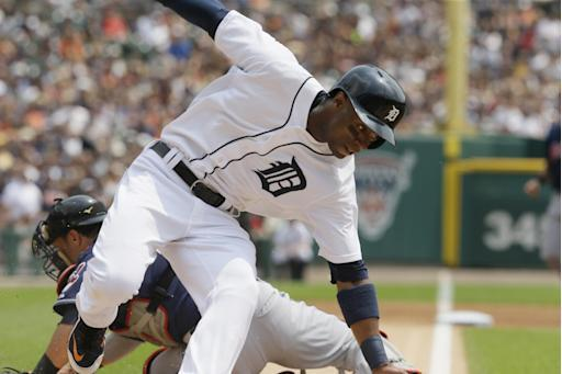Detroit Tigers' Austin Jackson, front, beats the tag of Cleveland Indians catcher Yan Gomes, back, and scores on teammate Ian Kinsler's single during the first inning of a baseball game, Sunday, July 20, 2014 in Detroit. (AP Photo/Carlos Osorio)