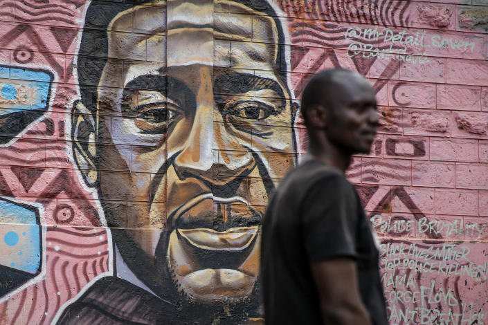 """A local resident stands next to a mural painted in June 2020 showing George Floyd with the Swahili word """"Haki"""" or """"Justice"""" in the Kibera low-income neighborhood of Nairobi, Kenya, Wednesday, April 21, 2021. After three weeks of testimony, the trial of the former police officer charged with killing George Floyd ended swiftly: barely over a day of jury deliberations, then just minutes for the verdicts to be read — guilty, guilty and guilty — and Derek Chauvin was handcuffed and taken away to prison. The guilty verdict in the George Floyd trial was not just America's victory. It signaled hope for those seeking racial justice and fighting police brutality across the Atlantic. (AP Photo/Brian Inganga)"""