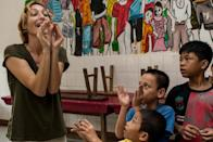 This picture taken on November 29, 2013, shows Italian violinist Sara Michieletto playing a game to improve attention skills and body language at a shelter for less fortunate children in Bekasi on the outskirts of Jakarta