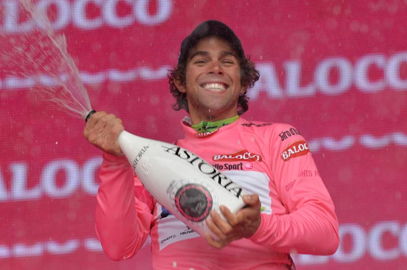 Australia's Michael Matthews sprays sparkling wine as he celebrates on the podium after clinching the overall leader's pink jersey at the end of the 218-kilometer (135-mile) second stage of the Giro d'Italia, Tour of Italy cycling race, from Belfast to Belfast, Northern Ireland, Saturday May 10, 2014. (AP Photo/Giuan Mattia D'Alberto)