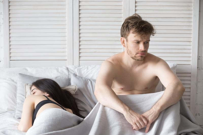 Young millennial attractive couple lying in bed under blanket at home. Woman sleeping, depressed and frustrated man thinking about relationships. Family have problems in sexual life impotence concept