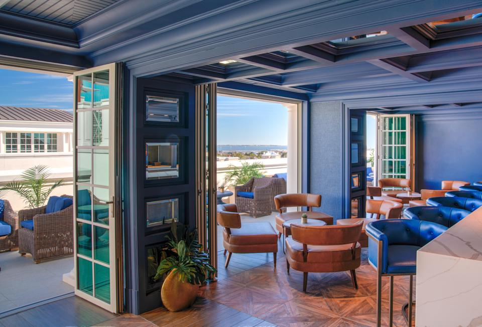 """<p><strong>Give us an overview of the space.</strong> There's a formal/casual symbiosis going on at this ninth-floor rooftop Champagne and cocktail bar. <a href=""""https://www.cntraveler.com/hotels/charleston/hotel-bennett?mbid=synd_yahoo_rss"""" rel=""""nofollow noopener"""" target=""""_blank"""" data-ylk=""""slk:The Bennett Hotel"""" class=""""link rapid-noclick-resp"""">The Bennett Hotel</a> is one of downtown Charleston's more refined spots, and the main bar interior reflects this. A regal dark purple palette dominates the space, with panelling that lands somewhere between Regency-era finery and a colorful spaceship. Patio doors lead to the far less buttoned-up terrace, and a deep blue pool surrounded by cabanas and seating. Views of Marion Square, King Street and St Matthews Lutheran Church stretching out below.</p> <p><strong>How's the crowd?</strong> As well as hotel guests topping up their cocktails as they lounge by the pool, there's a buzzy, post-work crowd of locals who are in-the-know enough to head straight here rather than the lobby bar. The somewhat-premium prices mean that it's a natural choice for special occasions, with birthday and anniversary drinks driving the popping of Champagne corks. It's mostly a well-dressed clientele, with swimming gear becoming less and less prevalent as the evening progresses.</p> <p><strong>How are the drinks?</strong> The house cocktails skew light and citrus-influenced, with infused vodkas and gins leading the way, perfect for hot and humid Charleston summers. Playful names—one of their signature drinks is called Don't Kale My Vibes—abound, and esoteric ingredients such as strawberry jam and dragon fruit make appearances. A compact but serviceable wine list and a host of locally-brewed beers back up the mixed drinks list.</p> <p><strong>What do they have for food?</strong> Complementing the cocktail list, the kitchen has a choice of light bites. A mezze platter, charcuterie and a poached pear salad are typically fresh options, and there's a coup"""