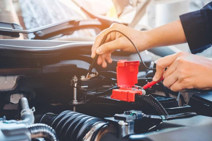 A mechanic in a repair shop tests a car battery's charge.