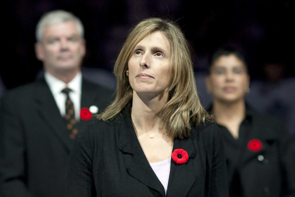 """FILE - In this Nov. 6, 2010, file photo, Cammi Granato stands on center ice after being inducted into the Hockey Hall of Fame before an NHL game between the Toronto Maple Leafs and the Buffalo Sabres in Toronto. Though Don Granato trails in the Granato family hockey pecking order behind brother Tony, who played 13 NHL seasons, and sister Cammi, a two-time Olympian, first female Hockey Hall of Fame inductee and NHL-expansion Seattle scout, Don Granato, now the Buffalo Sabres interim coach, became known by his siblings as """"the smart one."""" (Chris Young/The Canadian Press via AP, File)"""