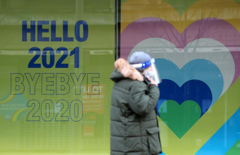 A shopper in Nottingham City Centre walks past a New Year sign. More than three quarters of England's population is being ordered to stay at home to stop the spread of coronavirus.
