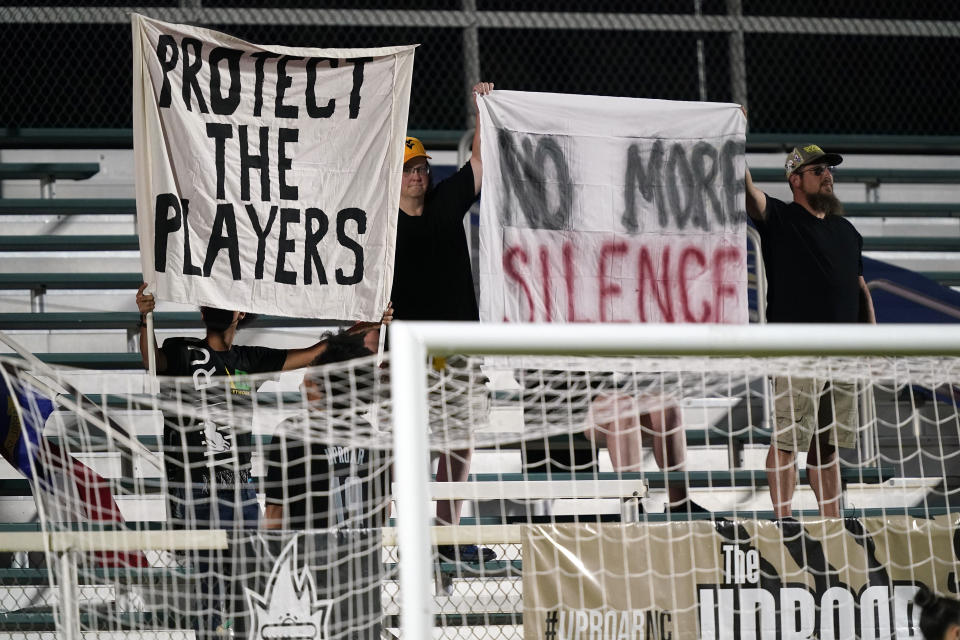 Fans hold signs during the first half of an NWSL soccer match between the North Carolina Courage and Racing Louisville FC in Cary, N.C., Wednesday, Oct. 6, 2021. (AP Photo/Gerry Broome)