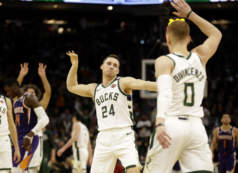 Milwaukee Bucks' Pat Connaughton (24) reacts with Donte DiVincenzo after DiVencenzo's three-point basket during the second half of an NBA basketball game against the Phoenix Suns, Sunday, Feb. 2, 2020, in Milwaukee. (AP Photo/Jeffrey Phelps)