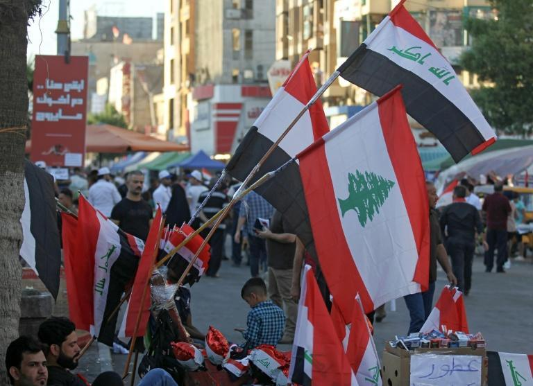 A Baghdad street vendor sells flags of Iraq and Lebanon, both gripped by anti-government protests
