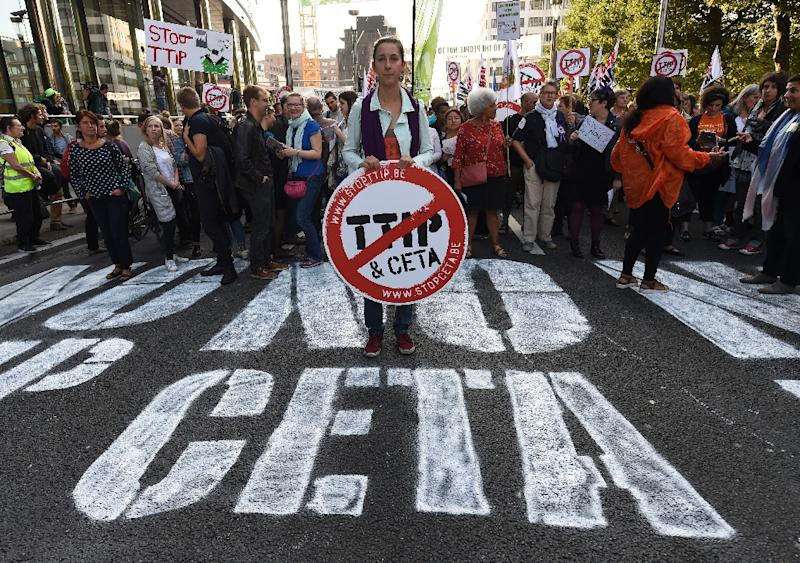 A woman holds an anti-TTIP and CETA placard during a demonstration outside the EU headquarters in Brussels, on September 20, 2016 to protest against huge transatlantic trade deals linking Europe with Canada and the US