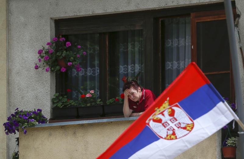 A woman standing at a balcony looks at a protest against Kosovo police action in the northern Serb-dominated part of ethnically divided town of Mitrovica, Kosovo, Wednesday, May 29, 2019. Russia and Serbia have blamed NATO and the West for an armed raid by Kosovo police in the Serb dominated north of Kosovo when a Russian U.N. employee was among more than two dozen people arrested in what Kosovo says was an anti-organized crime operation. (AP Photo/Visar Kryeziu)