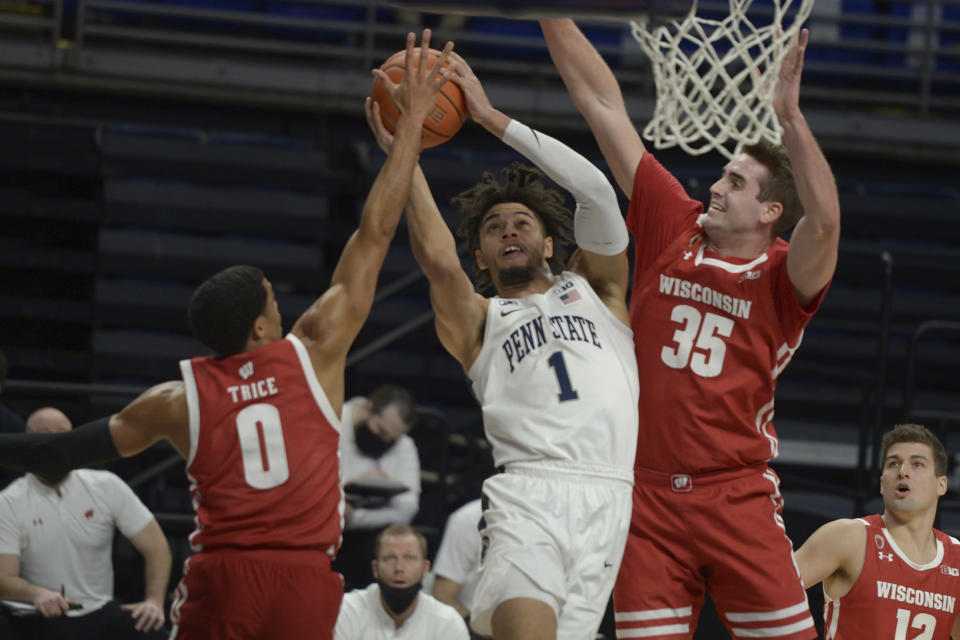 Penn State's Seth Lundy (1) goes to the basket splitting Wisconsin defenders D'Mitrik Trice (0) and Nate Reuvers (35) during the first half of an NCAA college basketball game, Saturday, Jan. 30, 2021, in State College, Pa. (AP Photo/Gary M. Baranec)