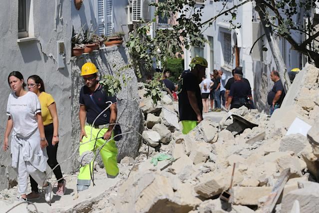 <p>Rescuers teams walk near a damaged building in one of the more heavily damaged areas on Aug. 22, 2017 in Casamicciola Terme, Italy. (Photo: Marco Cantile/NurPhoto via Getty Images) </p>