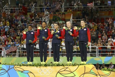 2016 Rio Olympics - Artistic Gymnastics - Final - Women's Team Final - Rio Olympic Arena - Rio de Janeiro, Brazil - 09/08/2016. (L-R) Simone Biles (USA) of USA, Gabrielle Douglas (USA) of USA (Gabby Douglas), Laurie Hernandez (USA) of USA, Madison Kocian (USA) of USA, Alexandra Raisman (USA) of USA (Aly Raisman) pose with their gold medals on the podium after winning the women's team final. REUTERS/Mike Blake