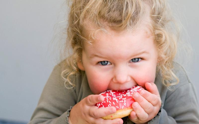 Young girl eating doughnut - Getty Images Contributor