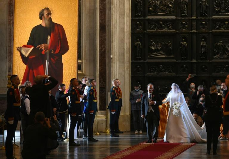 Victoria Romanovna Bettarini is accompanied by her father during her wedding ceremony at Saint Isaac's Cathedral in Saint Petersburg (AFP/Olga MALTSEVA)