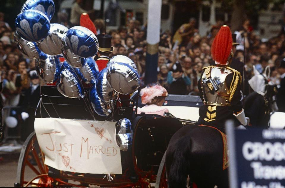 """<p>The newlywed's carriage was decorated with a """"Just Married"""" sign, as well as mylar balloons with the Prince of Wales feather on them. </p>"""