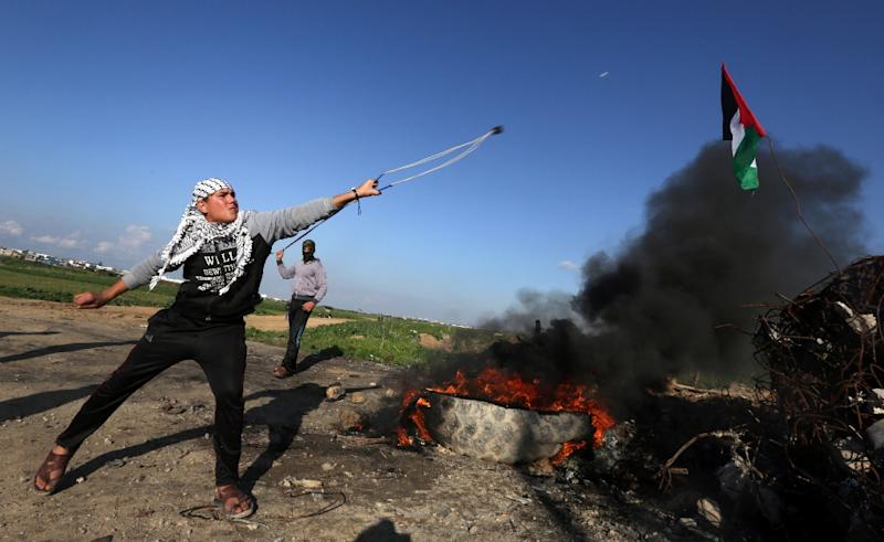 A Palestinian protester hurls a rock towards Israeli security forces during clashes near Shejaiya, an eastern district of Gaza City, along the border fence with Israel on December 18, 2015