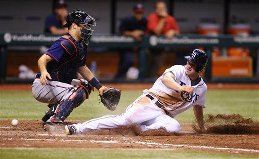 Tampa Bay Rays' Wil Myers, right, scores in front of Minnesota Twins catcher Joe Mauer on a sacrifice fly by Yunel Escobar during the eighth inning of a baseball game Monday, July 8, 2013, in St. Petersburg, Fla. (AP Photo/Brian Blanco)