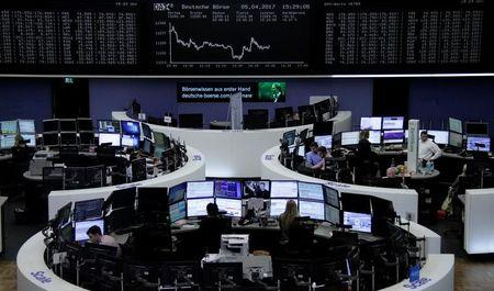 Traders work at their desks in front of the German share price index, DAX board, at the stock exchange in Frankfurt, Germany, April 5, 2017. REUTERS/Staff/Remote