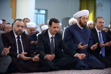 Syria's President Bashar al-Assad (2nd L) attends Eid al-Adha prayers at al-Nu'man bin Bashir mosque in Damascus October 4, 2014, in this handout photograph released by Syria's national news agency SANA. REUTERS/SANA/Handout via Reuters