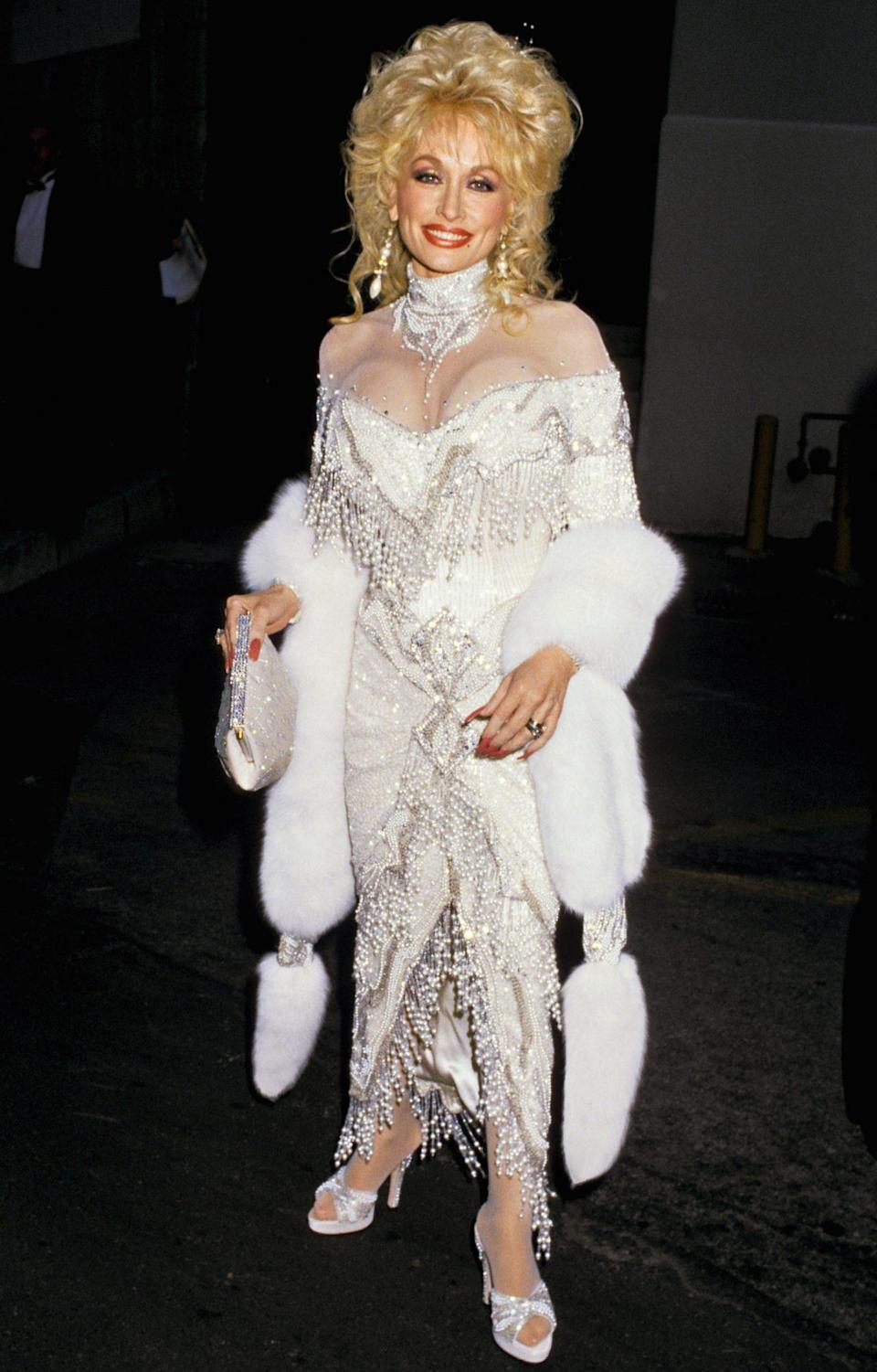 """<p>Her fashion — bust-baring, sparkly and unapologetically tight — has served as Parton's Trojan horse. """"I look like a woman, but I think like a man,"""" she's said, pictured here in 1988. """"And in this world of business, that has helped me a lot. Because by the time they think that I don't know what's goin' on, I got the money, and I'm gone!""""</p>"""