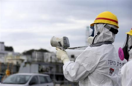 TEPCO employee uses a survey meter at the tsunami-crippled TEPCO's Fukushima Daiichi nuclear power plant