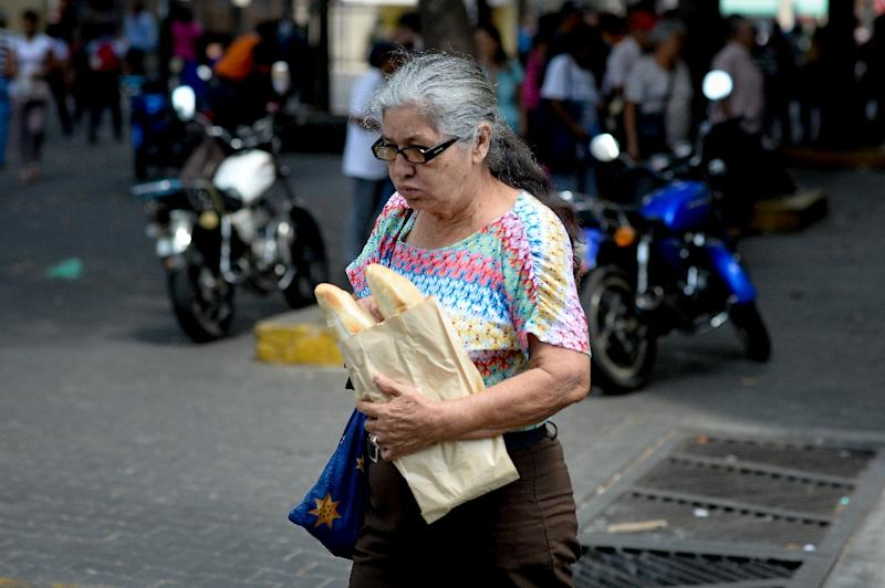 """The few bakeries that can still get hold of a 50-kilogram (110-pound) sack of flour to make bread limit their sales to just two """"canillas"""" -- thin half-baguettes -- per person three times a day (AFP Photo/Federico Parra)"""