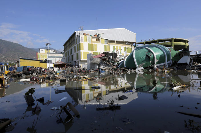<p>People survey the shopping mall damage following earthquakes and a tsunami in Palu, Central Sulawesi, Indonesia, Sunday, Sept. 30, 2018. A tsunami swept away buildings and killed hundreds on the Indonesian island of Sulawesi. (Photo: Tatan Syuflana/AP) </p>
