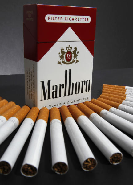 In this July 17, 2012 photo, Marlboro cigarettes are displayed in Montpelier, Vt. Marlboro maker Altria Group Inc.'s third-quarter net income fell 44 percent on charges for a loss on early extinguishment of debt. But it sold more cigarettes at higher prices and expanded its industry-leading share of the U.S. market. The owner of the nation's biggest cigarette maker, Philip Morris USA, on Thursday, Oct. 25, 2012, reported net income of $657 million, or 32 cents per share, for the three-month period ended Sept. 30, down from $1.17 billion, or 57 cents a share, a year earlier. (AP Photo/Toby Talbot)