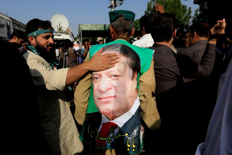 FILE PHOTO: A supporter of former Prime Minister Nawaz Sharif touches his picture as he celebrate with others following the court's decision in Islamabad, Pakistan