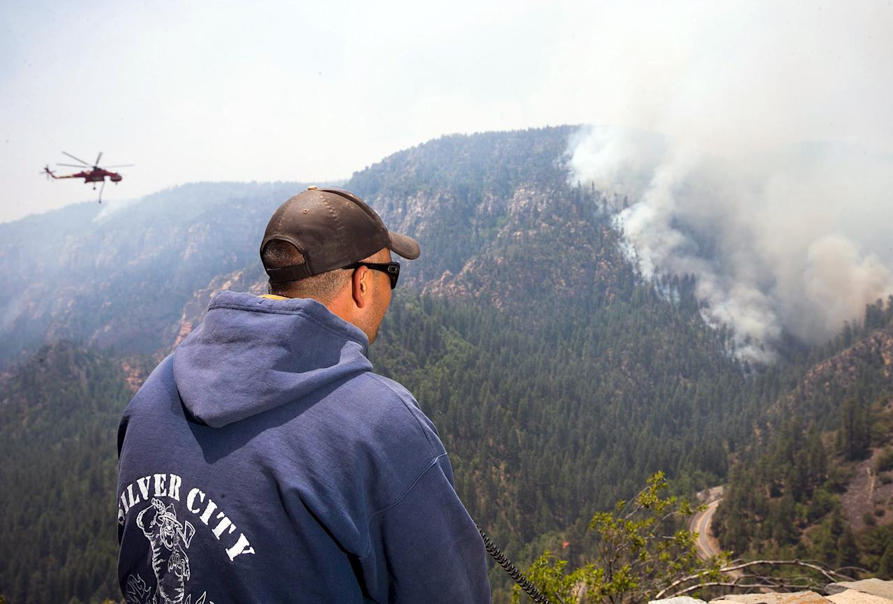 A Sante Fe Hot Shot works as a lookout as he oversees part of the Slide Fire in Sterling Canyon at the Oak Creek Overlook above Sedona, Ariz., on Thursday, May 22, 2014. Hundreds of firefighters worked Thursday to protect communities on the edge of Flagstaff from a wildfire that is chewing up a scenic Arizona canyon with towering flames and burning entire trees down to nothing but ash. (AP Photo/The Arizona Republic, Michael Schennum) MARICOPA COUNTY OUT; MAGS OUT; NO SALES
