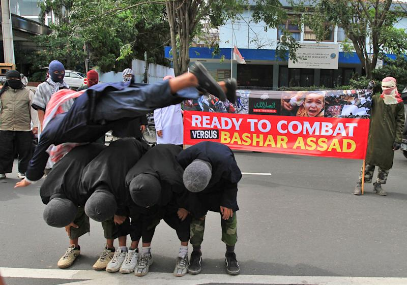 In this Sunday, June 9, 2013 photo, militants, who claimed that they are ready depart to fight the war in Syria, perform martial art techniques during a show of force in Solo, Central Java, Indonesia. While security agencies in Europe and beyond are worried about militants returning from Syria, Indonesia knows only too well how foreign battlefields, training opportunities and contact with al-Qaida can lead to deadly results. Indonesian anti-terror officials estimated there were around 50 Indonesian militants fighting against the regime of Bashar Assad in Syria and the number is expected to grow. (AP Photo)