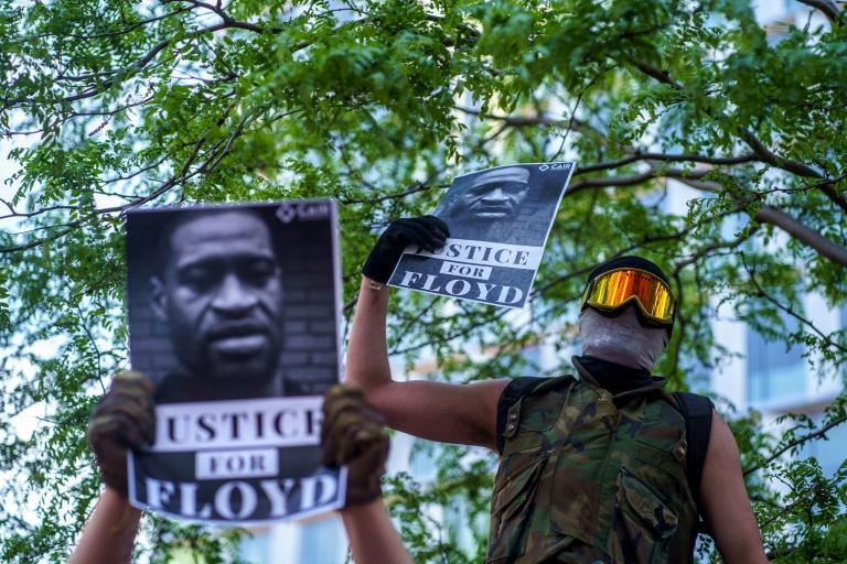 A masked protester in the US city of Minneapolis holds a sign demanding justice for George Floyd, the African-American man who died in police custody on May 25, 2020, sparking fiery riots and accusations of police racism