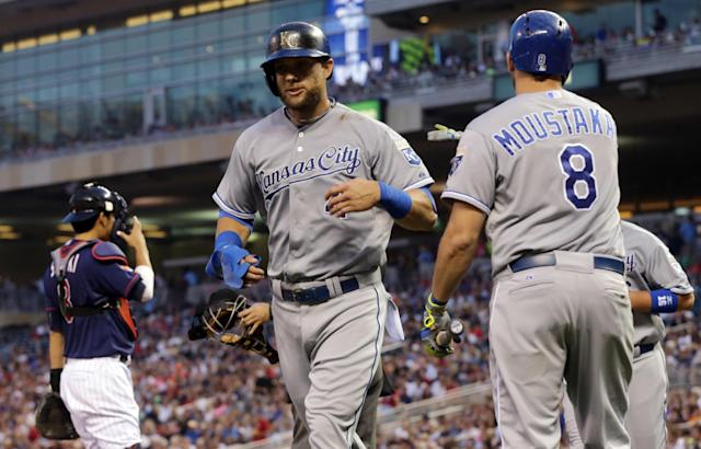 Kansas City Royals' Alex Gordon, center, returns to the dugout after scoring on a three-run double by Josh Willingham off Minnesota Twins pitcher Ricky Nolasco in the fourth inning of a baseball game, Friday, Aug. 15, 2014, in Minneapolis. (AP Photo/Jim Mone)