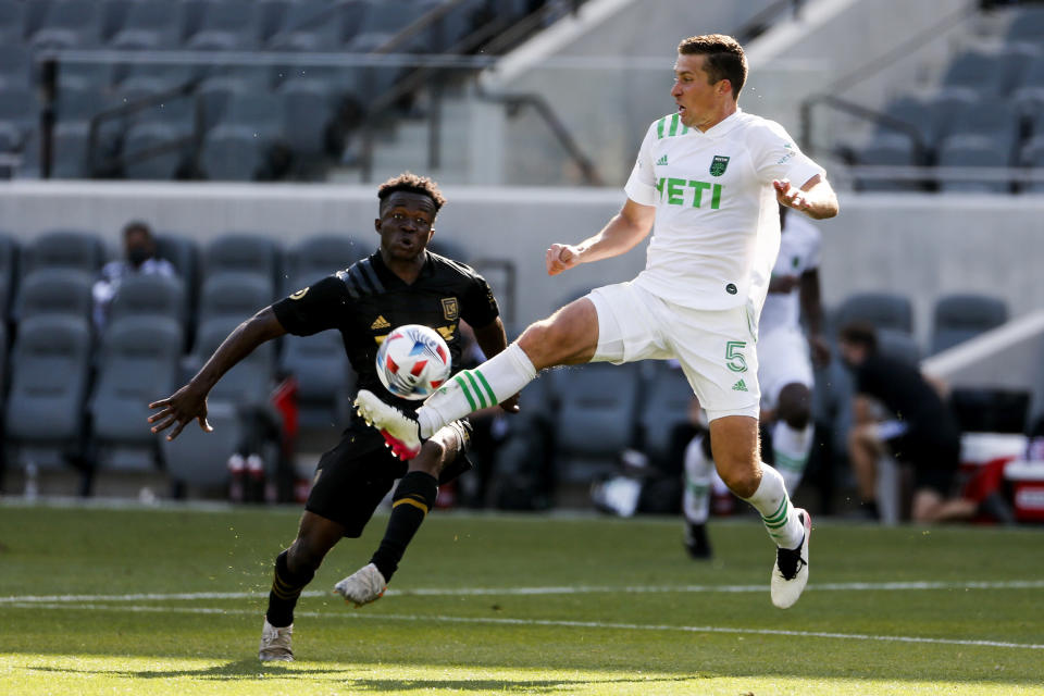 Austin FC defender Matt Besler (5) controls the ball next to Los Angeles FC forward Kwadeo Opoku during the second half of an MLS soccer match Saturday, April 17, 2021, in Los Angeles. (AP Photo/Ringo H.W. Chiu)
