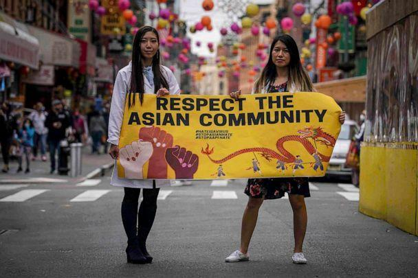 PHOTO: Dr. Michelle Lee, left, a radiology resident, and Ida Chen, right, a physician assistant student, unfold a banner Lee created to display at rallies protesting anti-Asian hate in the Chinatown area of New York, April 24, 2021. (Bebeto Matthews/AP)