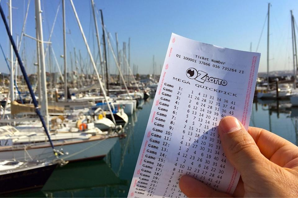 Hand holds OzLotto ticket in front of a marina. Source: The Lott