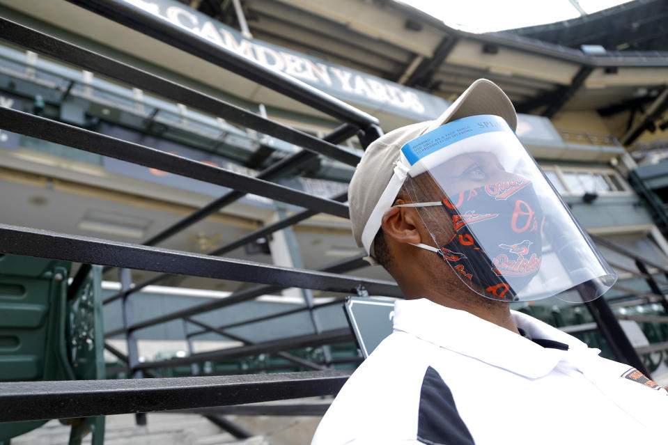 A security officer uses a face mask and shield to protect against the new coronavirus while assisting at Baltimore Orioles baseball training camp, Friday, July 3, 2020, in Baltimore. (AP Photo/Julio Cortez)